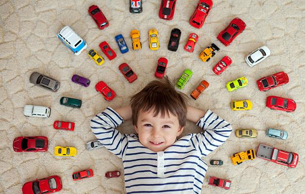 niño con coloridos coches de juguete