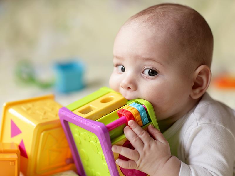 Niño con juguete con formas y colores.